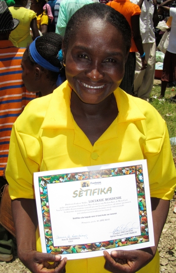 "Locianie Bondesir shows off her certificate after graduating from CLM. Locianie says of her accomplishment: ""Now, I can find money. We eat three times a day. I can pay for school for my children; I buy books each time they ask me. I have succeeded."""