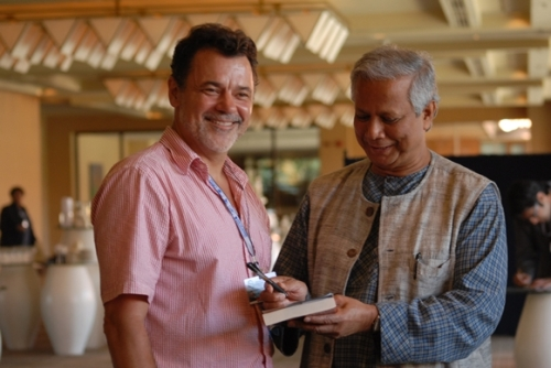 Muhammad Yunus signs the MicroFinance Transparency endorsement at the 2008 Summit in Bali with Chuck Waterfield. Smiles abound._581x389