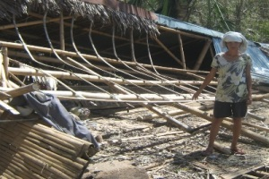 An Ahon Sa Hirap Inc. client in front of her destroyed house