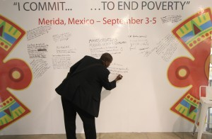 A Summit delegate writes on the Commitment Wall at the 17th Microcredit Summit