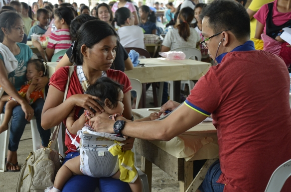 A doctor provides free checkups as part of a health outreach program in the Philippines. Photo by: CARD MRI