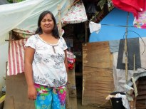 A CARD client in Tacloban stands in front of her temporary tarp and plywood shelter.