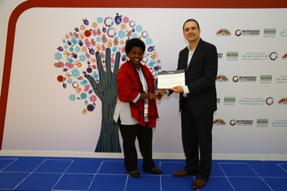 Antonio handing the Oradian winner certificate to the representative of Vicoba Village Community Bank from Tanzania